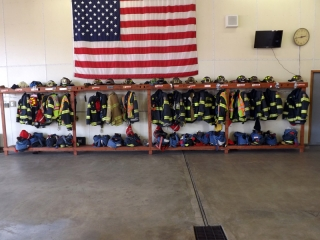 Cortland Fire Department uniforms along a wall
