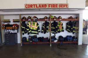Cortland Fire Department uniforms along a wall