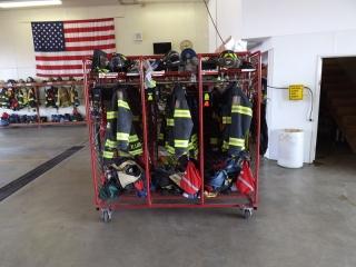 Cortland Fire Department uniforms on a cart